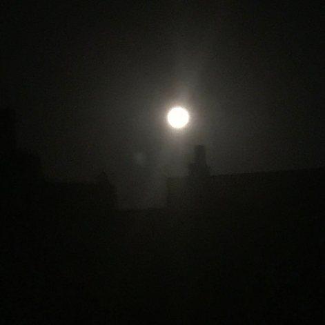La Lune ronde et pleine au-dessus des toits